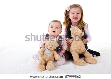 A cute baby girl is sitting on the floor next to a basket of teddy bears. Horizontal shot. - stock photo