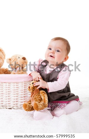 A cute baby girl is sitting on the floor next to a basket of teddy bears. Vertical shot.