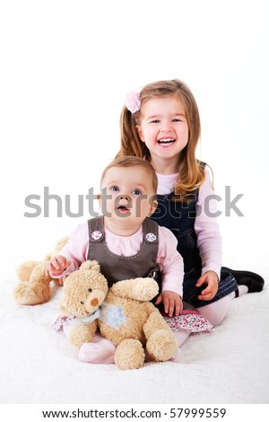 A cute baby girl is sitting on the floor next to a basket of teddy bears. Vertical shot. - stock photo