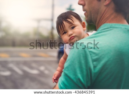 A cute baby girl looks over her dad'?s shoulder to see what's going on.  - stock photo