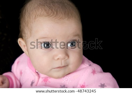 A cute baby girl on a black background