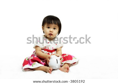 A cute baby girl playing with a piggy bank