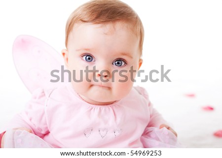 A cute baby girl wearing fairy wings stares wide-eyed at the camera.  Horizontal shot. - stock photo
