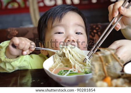a cute baby is eating - stock photo