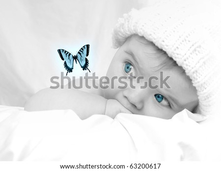 A cute baby is wearing a white hat on a soft background with blankets. The child is staring at a butterfly fluttering. Use for a imagination, growth or childhood theme.