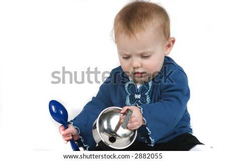 A cute baby playing with pots and a spoon on white background - stock photo