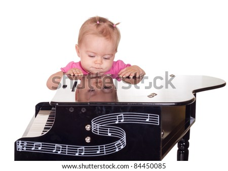A cute baby plays with a piano. - stock photo