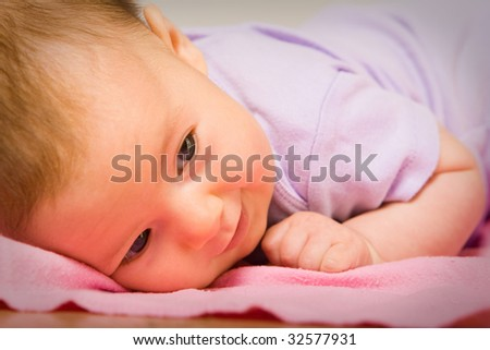 A cute baby smiling on a bed closeup portrait - stock photo