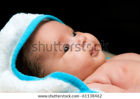 A cute baby with a towel on its head on a black background