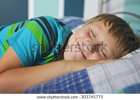 A cute boy having good time on bed.