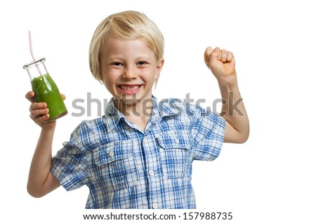 A cute boy holding a bottle of green smoothie or juice is flexing his muscles and smiling. Isolated on white. - stock photo