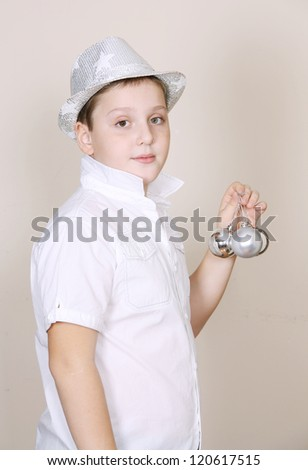A cute boy in a holiday silver hat and with silver baubles - stock photo