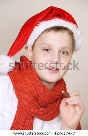 A cute boy in a red christmas hat and scarf  eating a chocolate - stock photo