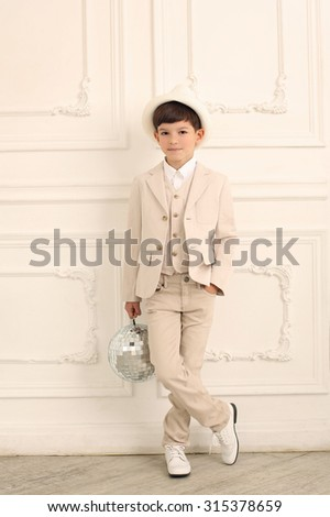 A cute boy in white suit and hat.  Indoor - stock photo