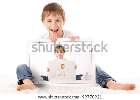 A cute  boy, sits on the floor, holding baby photographs of himself. The photographs are arranged such that the boy is holding a photo of his younger self, holding a photo of his baby self. - stock photo