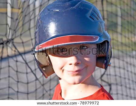 A cute boy with his helmet on waiting for his turn at batting practice. - stock photo