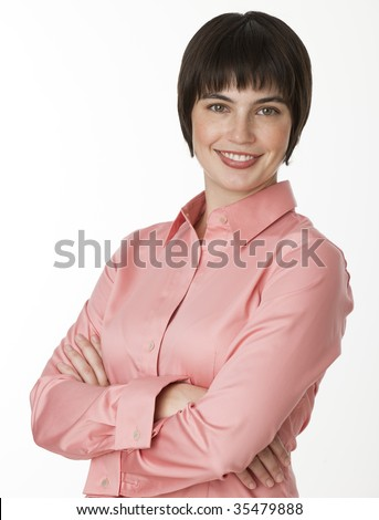 A cute brunette posing and smiling.  She has her arms crossed and is looking directly at the camera. Vertically framed shot.