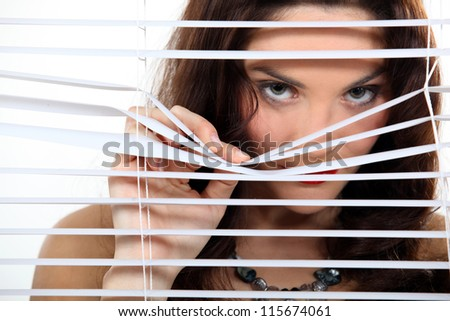 A cute brunette spying through the blinds. - stock photo