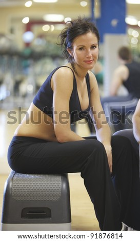 A cute brunette taking a break at the gym - stock photo