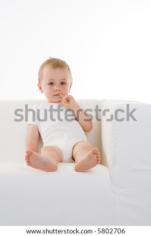 A cute caucasian baby with a finger in his teeth while sitting on a sofa.  Prominent theme colour is white.