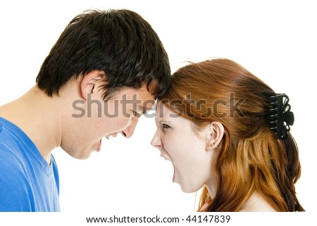 A cute Caucasian teenage girl and her Asian teen boyfriend yell at each other - stock photo
