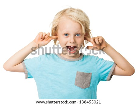 A cute cheeky young boy smiling and sticking his fingers in his ears. Isolated over white. - stock photo