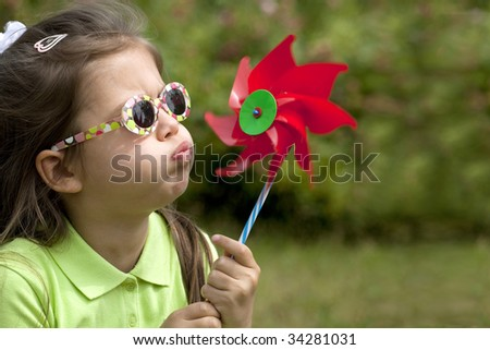 A cute child blowing a wind mill. - stock photo