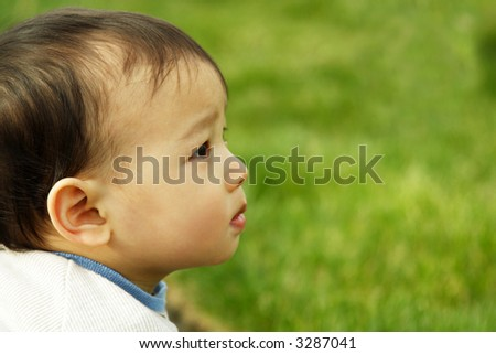A cute child outside on a grass field (copyspace) - stock photo