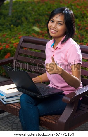 A cute college student using a laptop on a park bench gives a thumb up for success while beaming a radiant smile.  20s female Asian Thai model of Chinese descent. - stock photo