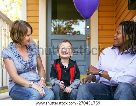 a cute diverse family sitting on a porch  - stock photo