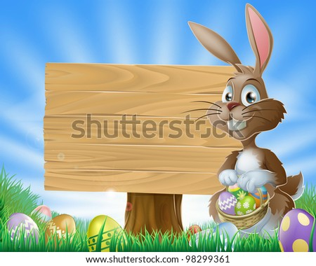 A cute Easter bunny rabbit character standing by a wooden sign holding a basket of decorated Easter eggs surrounded by Easter eggs in a field - stock photo