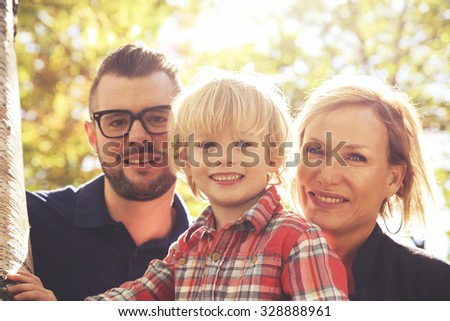 a cute family posing with the word love in a park toned with a retro vintage instagram filter effect app or action - stock photo