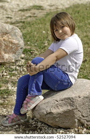 A cute five year old girl posing on a rock outside