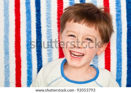 A cute four year old boy laughing - stock photo