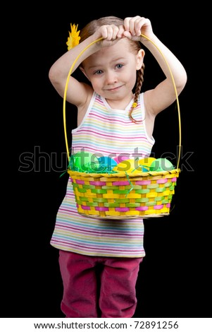 A cute girl holding up her colorful easter basket. - stock photo