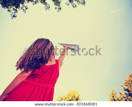 a cute girl in a red dress throwing a paper airplane into the sky while a real plane is passing overhead in a park during summer time toned with a retro vintage instagram filter app or action effect  - stock photo