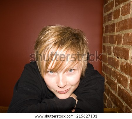 a cute girl in a restaurant next to a brick wall - stock photo