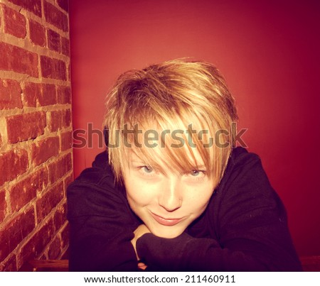 a cute girl in a restaurant next to a brick wall toned with a retro vintage instagram like filter  - stock photo