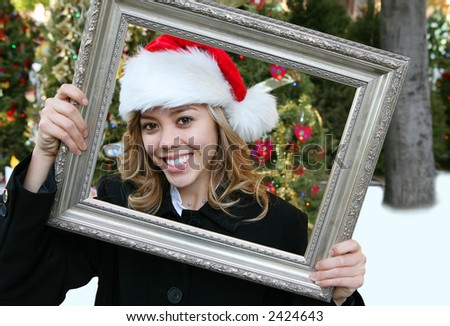 A cute girl in a santa hat at christmas holding a picture frame
