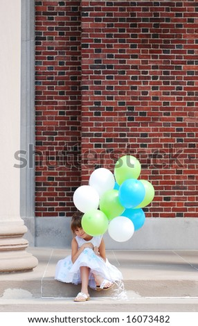 A cute girl peeking behind her balloons - stock photo
