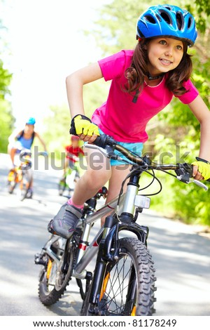A cute girl riding her bicycle with competitors far behind - stock photo