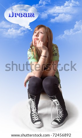 A cute girl sitting and thinking with a dreamy expression; blue sky and clouds background and text of the word DREAM in her thought bubble - stock photo