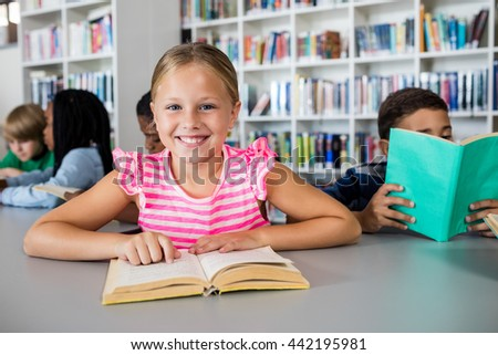 A cute girl smiling at the camera in library
