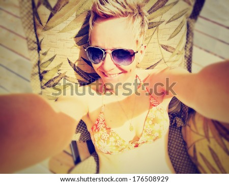 a cute girl smiling at the camera on a bright sunny day done with a retro vintage instagram filter - stock photo