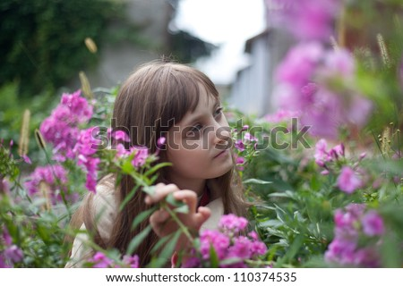 a cute girl  surrounded by flowers - stock photo