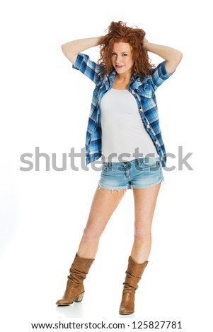 A cute girl wearing short denim shorts playing with her naturally curly red hair - stock photo