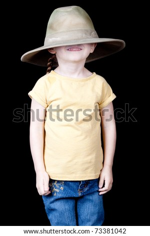 A cute girl with an oversized hat on her head.  It is pulled over her eyes.