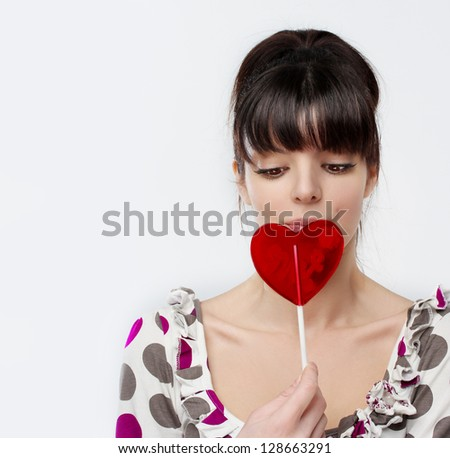 A cute girl with heart-shaped red lollipop in her hand. - stock photo