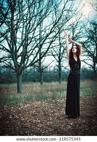 A cute goth girl wearing black dress stands amongst autumnal trees - stock photo