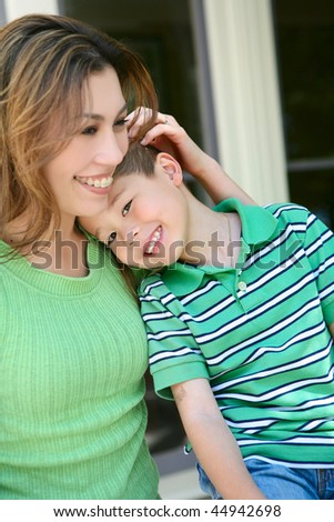 A cute happy boy and his mother on the porch at home showing love - stock photo